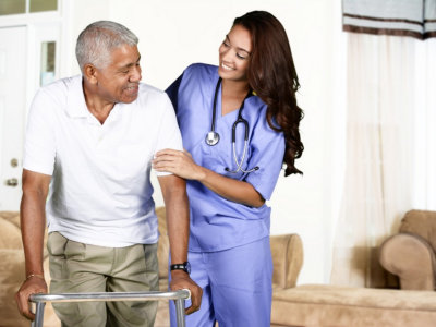 Caregiver helping elderly man to stand up