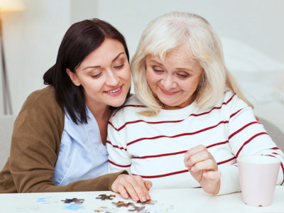 caregiver helping elderly woman complete a jigsaw puzzle