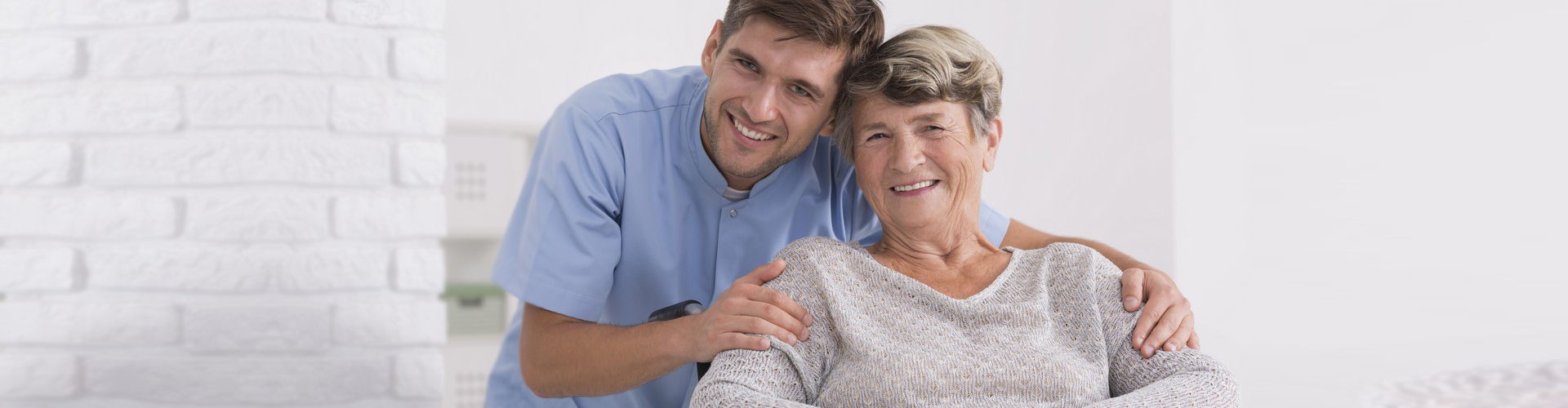 Caregiver smiling together with elderly woman